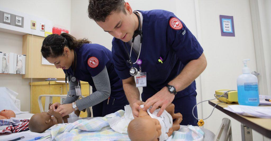 Một Điều dưỡng nam đang cẩn thận chăm sóc em bé